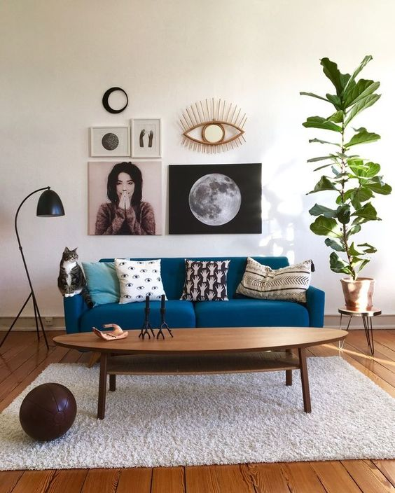 a monochromatic space with a classic blue sofa that adds color and a bright and fashionable touch to the space