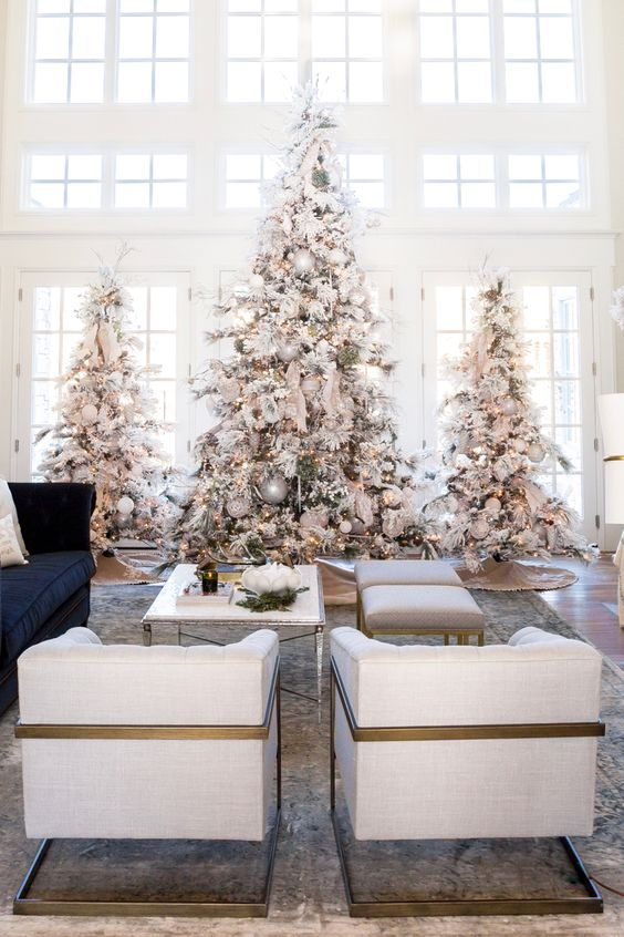 a trio of large flocked Christmas trees with lights, neutral and metallic ornaments for a winter fairy-tale in the space