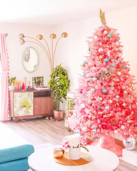 a bright pink Christmas tree with pastel and metallic ornaments and a large gold star topper for infusing your space with color