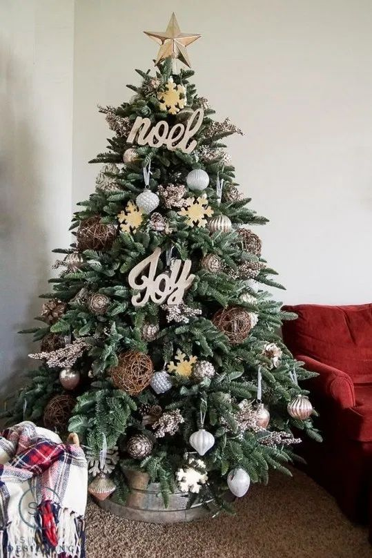 a farmhouse Christmas tree with metallic and oversized vine ornaments, wooden signs and snowflakes plus a galvanized bucket base