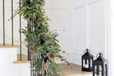 11 a lush evergreen garland with pinecones and berries plus large bells will make your staircase super festive