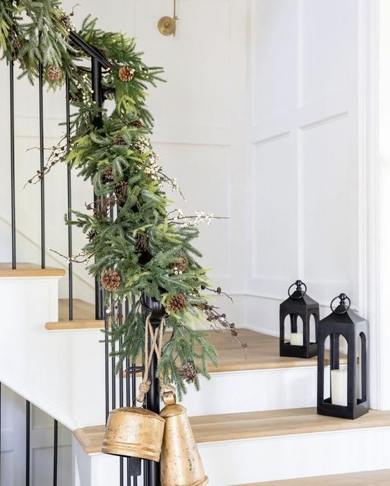 a lush evergreen garland with pinecones and berries plus large bells will make your staircase super festive