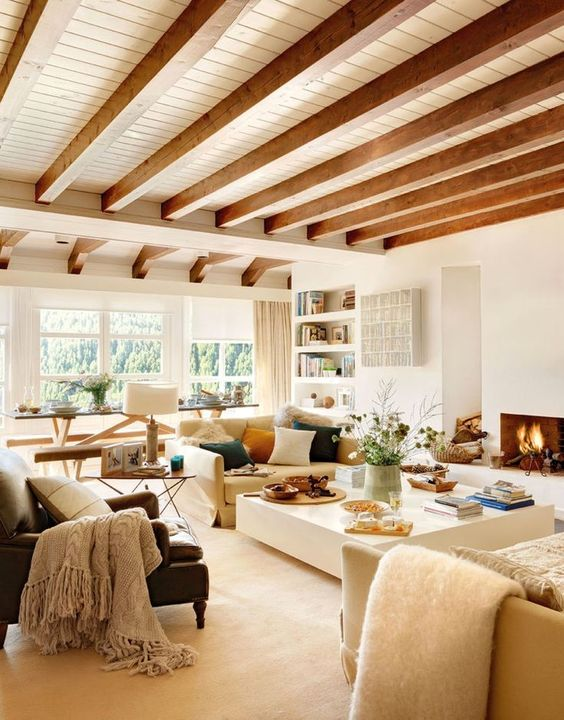a neutral yet warm-toned living room done with whites and wooden beams on the ceiling for a touch of nature