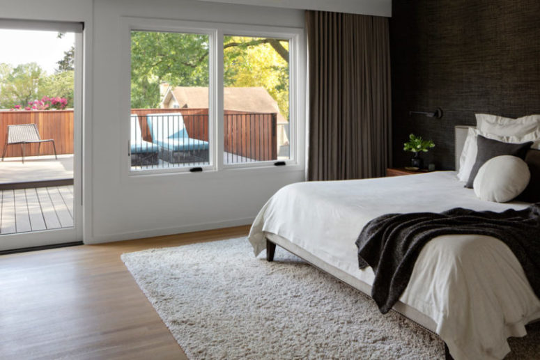 The bedroom is done with a black wall, a monochromatic bed and textiles, there's an entrance to a terrace
