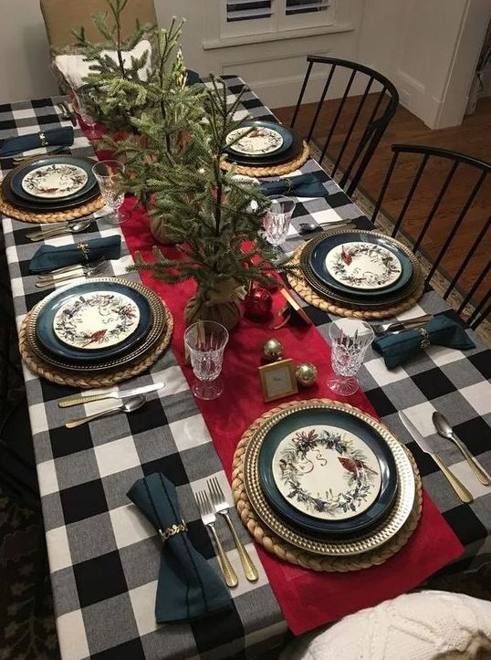 a buffalo check tablecloth with a red runner make the table look a bit retro and very stylish at the same time