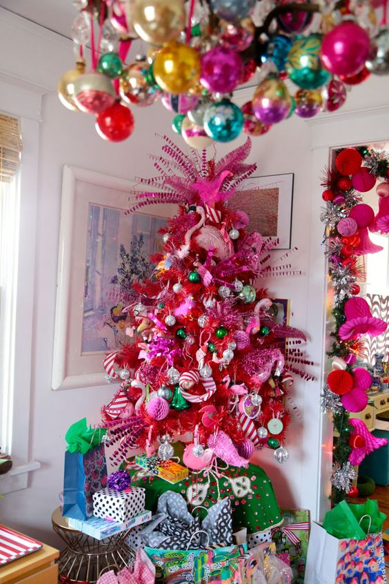 a crazy hot pink Christmas tree with metallic, green and pink ornaments, pink flamingos and striped ribbons