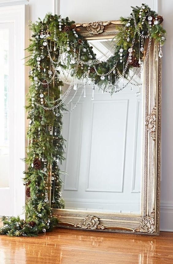 a lush evergreen garland with pinecones and crystals plus bead covers the large mirror bringing a strong Christmas feel to the space