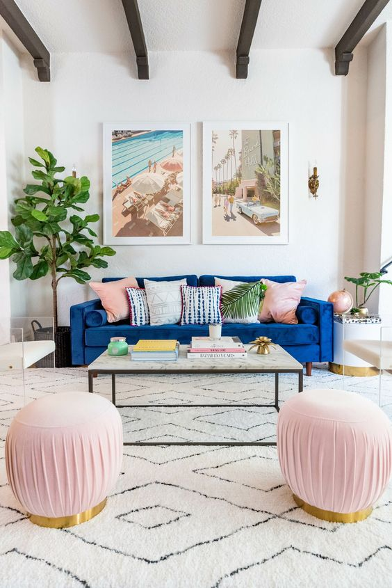 a neutral and pastel living room with a classic blue sofa that adds a bright touch and statement to the space