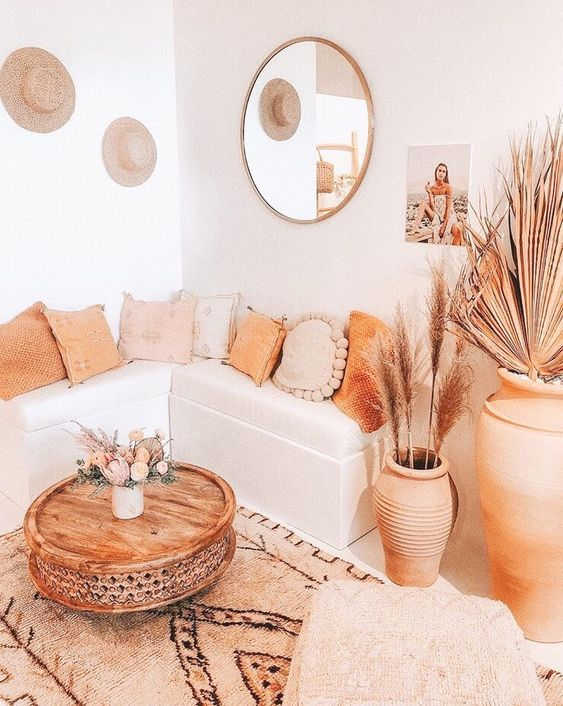 a neutral and warm-toned boho living room with warm touches, rugs, a table and a terra cotta pot plus pampas grass