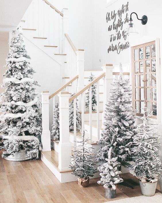 a winter wonderland entryway with multiple flocked trees with some white decor looks very dreamy