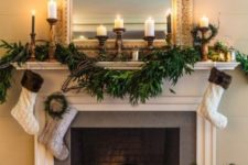 13 a lush greenery garland and neutral stockings hanging down plus pillar candles in wooden candleholders for elegant styling