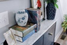 13 a navy IKEA Hemnes shoe cabinet with a marble contact paper top and cool geometric knobs looks very chic and contemporary