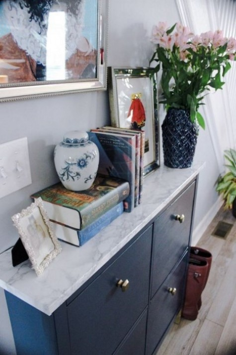 a navy IKEA Hemnes shoe cabinet with a marble contact paper top and cool geometric knobs looks very chic and contemporary