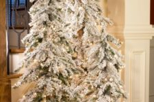 13 create a winter wonderland with a trio of flocked Christmas trees with lights and some white fabric at the base