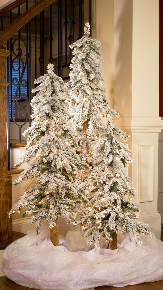 create a winter wonderland with a trio of flocked Christmas trees with lights and some white fabric at the base