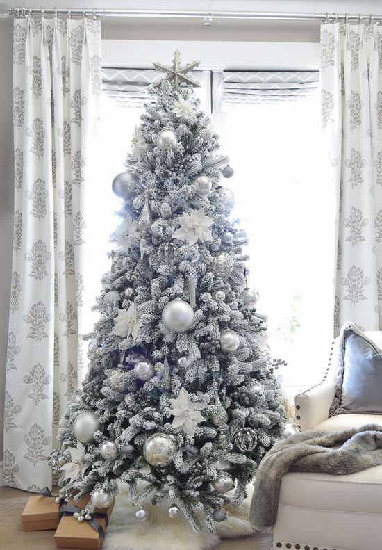 a flocked Christmas tree with silver and silver glitter usual and oversized Christmas ornaments looks frozen