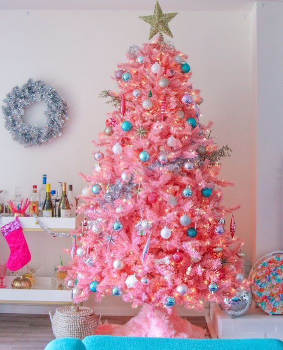 a hot pink Christmas tree with neutral, metallic and blue ornaments and lights