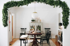 14 a lush greenery garland covering the doorway to bring a slight and chic Christmas feel to the space