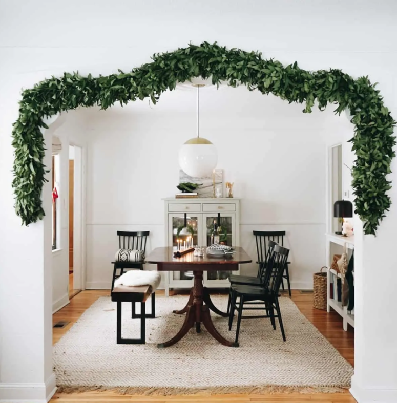a lush greenery garland covering the doorway to bring a slight and chic Christmas feel to the space