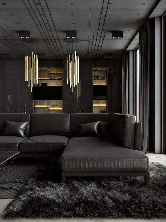 a luxurious dark living room with a large black sectional sofa, a faux fur rug, statement gold chandeliers and raw concrete