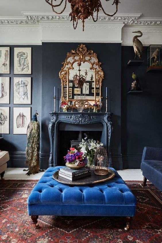a refined and chic living room with a classic blue ottoman that adds color and a bold touch to the space