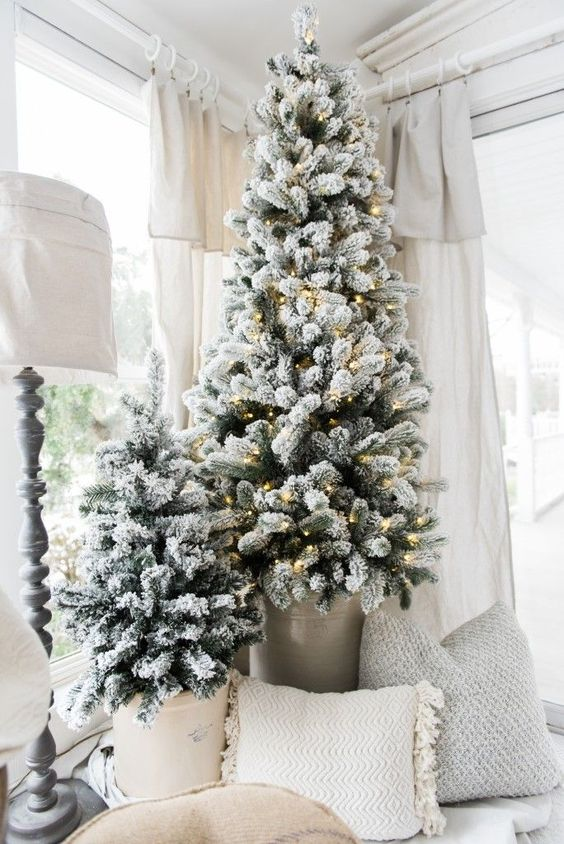 flocked Christmas trees in buckets, one of them is decorated with lights look very nice a neutral farmhouse space