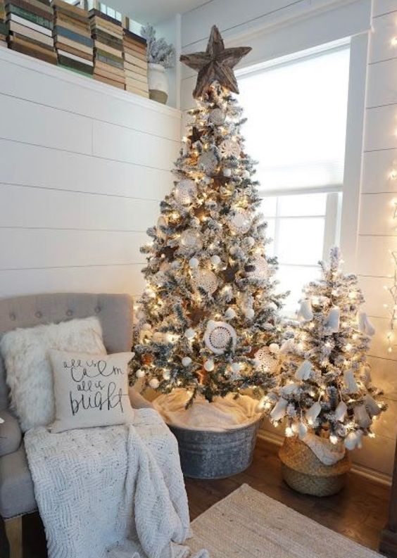 a cute duo of flocked Christmas trees with lights, white ornaments and pompoms for a neutral space