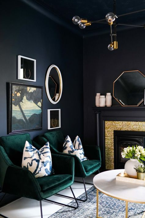 a dark and super elegant living room in black, with gold touches and dark green chairs looks refined