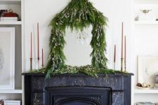 15 a lush greenery garland with mini ornaments covering a mirror on the mantel adds a quirky holidya touch to the space