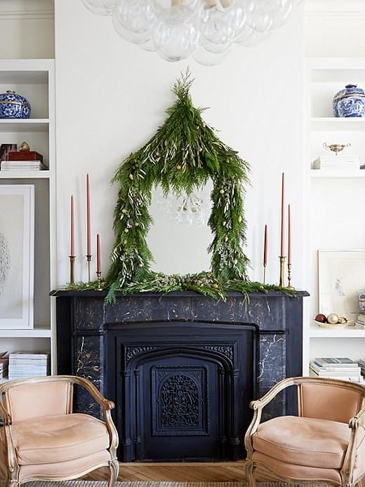 a lush greenery garland with mini ornaments covering a mirror on the mantel adds a quirky holidya touch to the space