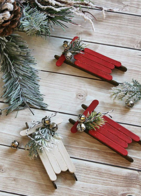 red and white Christmas ornaments of popsicle sticks with evergreens and bells will bring a rustic and vintage feel