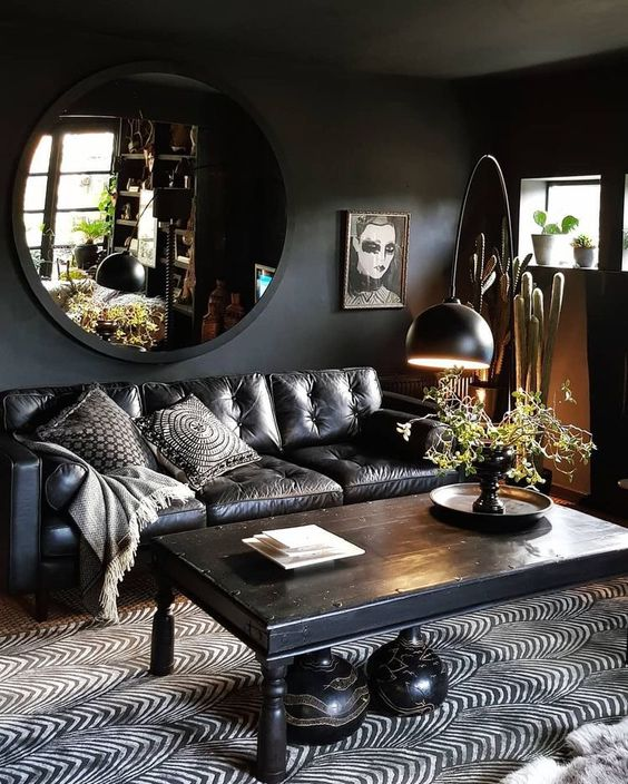 a dark living room with a boho feel, a printed rug and quirky artworks and pillows