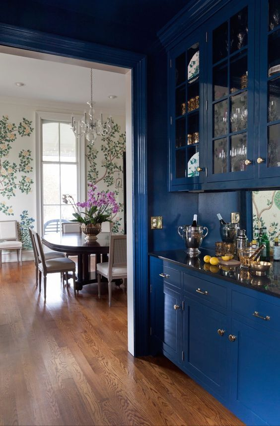 a home bar with classic blue cabinets with glass doors looks chic and refined and adds a trendy touch to the space