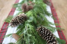16 a lush greenery garland with pinecones is a cool table decoration for Christmas