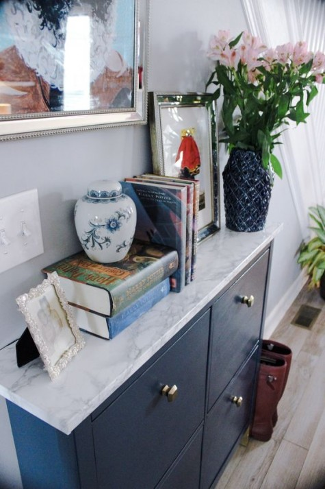 a navy IKEA Hemnes shoe cabinet with navy paint and some marble contact paper plus brass knobs to get a stylish look