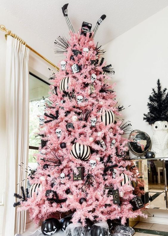 a pastel pink Christmas tree with black and white ornaments, skulls, witches' legs and a vintage cameras for a Halloween-inspired tree