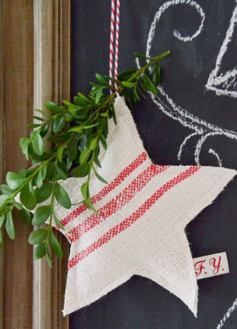 a striped red and white Christmas star ornament with evergreens and red and white twine is a traditional idea