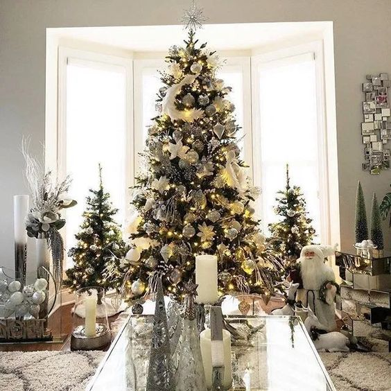 a trio of elegant and chic Christmas trees decorated with lights and white and silver ornaments and feathers