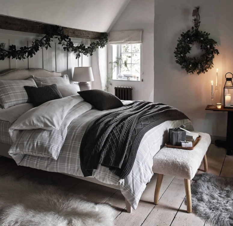 a simple greenery garland over the bed plus a matching wreath on the wall bring a slight Christmas feel to the space