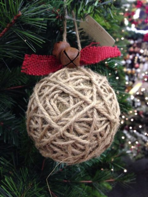 a twine wrapped Christmas ornament with red burlap and rust bells is a nice rustic idea with an eye-catchy accent