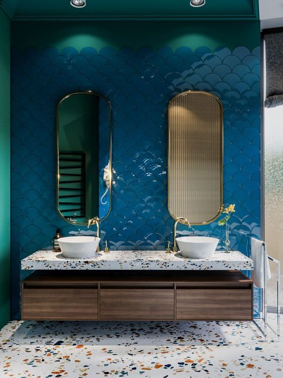 a bold bathroom with a classic blue fish scale tile wall and terrazzo countertops and a floor for a cool look