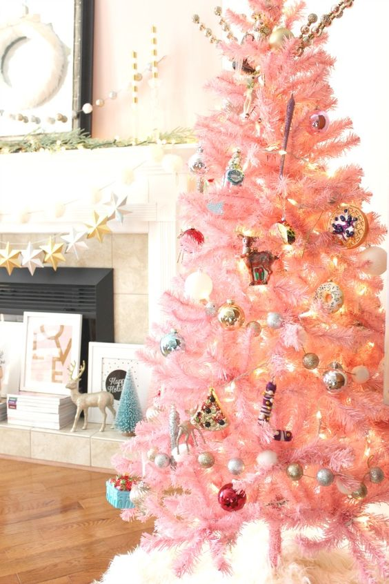 a pastel pink Christmas tree with metallic ornaments, lights and retro ones looks as a cute and chic touch of color