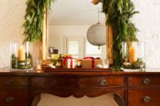 18 a vintage buffet covered with a lush greenery garland, with gold ornaments on red ribbons plus gift boxes looks very chic