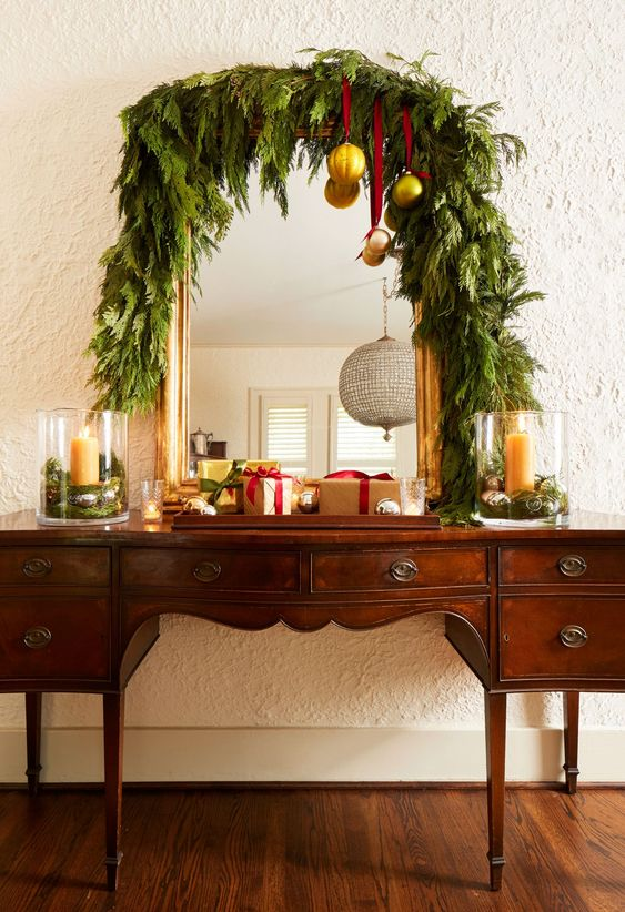 a vintage buffet covered with a lush greenery garland, with gold ornaments on red ribbons plus gift boxes looks very chic