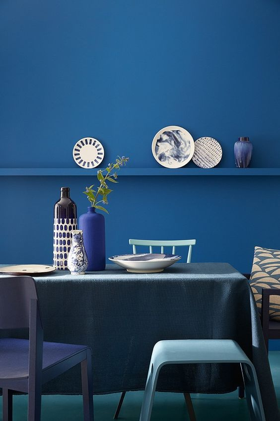 a contemporary dining space with a classic blue wall with a ledge, tuquoise chairs and a grey tablecloth