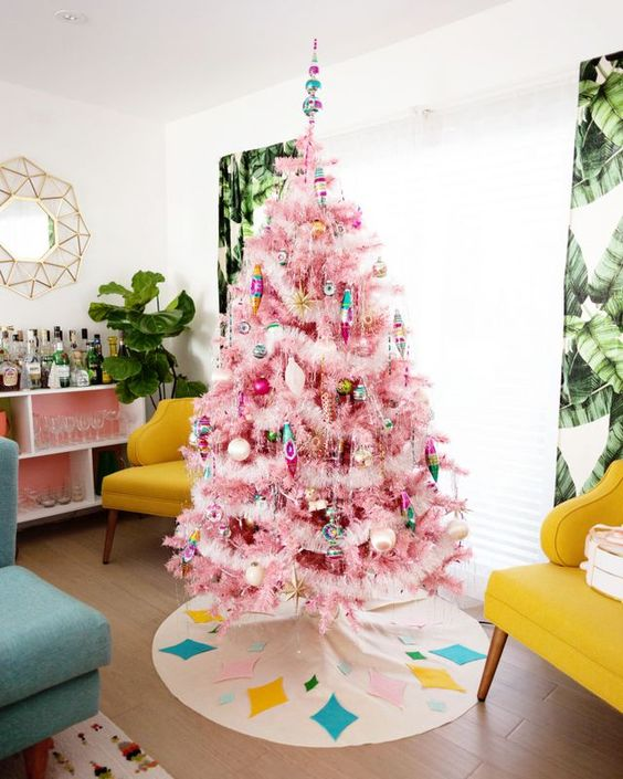 a pink Christmas tree decorated with pastel and colorful ornaments and fluffy stuff plus a bright topepr looks retro