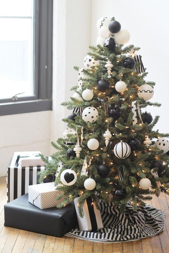 a stylish modern Christmas tree with lights and printed oversized black and white ornaments plus a striped skirt