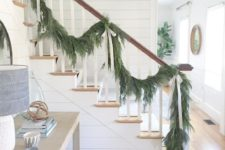 19 an evergreen garland with neutral silk bows to decorate the railing is a stylish and beautiful idea