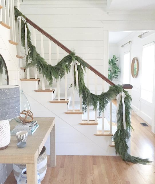 an evergreen garland with neutral silk bows to decorate the railing is a stylish and beautiful idea