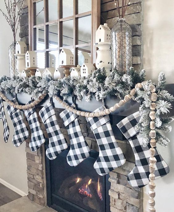 buffalo check stockings, flocked evergreens and wooden bead garlands for Christmas mantel decor